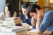 Student falling asleep at desk in college library