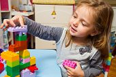 Little Girl Is Playing With Building Bricks
