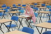 Student sitting at desk ain empty exam hall while smiling