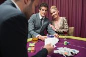 Couple playing poker and smiling in casino