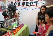SUBANG JAYA - NOVEMBER 10: Unidentified visitors watch a robot interact with them at the World Robot