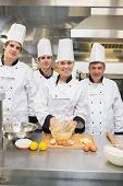 Smiling culinary students with pastry teacher in kitchen