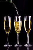 Two full glasses of champagne and one being filled against black background
