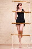 Beautiful young woman in black holds on bamboo rope ladder and looks up.