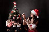 Santa girl decorates Christmas tree.