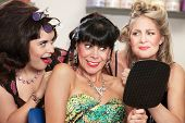 stock photo of snob  - Grinning woman and friends with mirror in hair salon - JPG