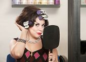 stock photo of snob  - Caucasian woman in curlers with mirror feeling her hair - JPG