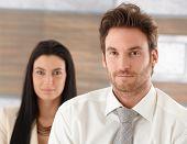 Retrato do jovem empresário de bem parecido, a mulher em pé no fundo.