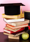 Books and magister cap against school board on wooden table on pink background