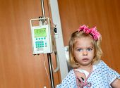 foto of intravenous  - Recovering Little baby girl hospitalized with a Intravenous bag on a pole - JPG