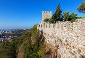 stock photo of fortified wall  - Perimeter fortified stone wall with a lookout tower and crenellations of a castle or fortified walled medieval town with a view out over the valley below - JPG