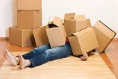 stock photo of box-end  - Man covered by lots of cardboard boxes  - JPG