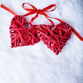 Picture of two beautiful romantic vintage red hearts tied together with a ribbon on a white snow background. Love and st. Valentines day concept.
