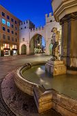 Brunnenbuberl Fountain And Karlstor Gate In The Evening, Munich, Germany
