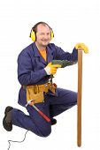 Worker in ear muffs with drill and board