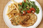 breaded chicken schnitzels or escalopes with french fries and a tomato and green salad