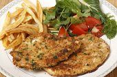 breaded homemade chicken schnitzels or escalopes with french fries and a tomato and green salad