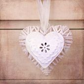 A wicker and a tin heart hanging from the knob of a chest of drawers. Vintage effect with added text