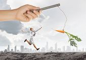 stock photo of dangling a carrot  - Funny image of businesswoman chased with carrot - JPG