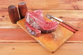 fresh raw uncooked beef fillet mignon entrecote on board prepared for cooking on wood table with cutlery and castors