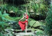 Young and beautiful ballerina in red dress dancing with the blowing silk on the beach