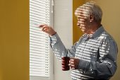 picture of jalousie  - Senior man with cup looking out the window through jalousie - JPG