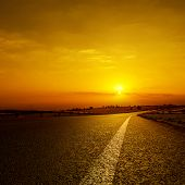 asphalt road to orange horizon in sunset