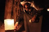 DAHAB, EGYPT - JANUARY 24, 2011: Bedouin sits by the light at night. Bedouin culture still survives