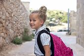 image of bagpack  - A young child with school uniform and bagpack outside smiling positive looking at camera - JPG