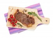 Sirloin steak with rosemary and cherry tomatoes on a cutting board. Isolated on white background. View from above