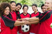 Portrait of confident female soccer team stacking hands on ball at park