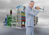 Furious businessman posing with loudspeaker against cloudy dull sky