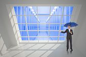 Peaceful businessman holding blue umbrella against server hallway seen through window
