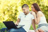 Happy Beautiful Couple Using Laptop Outdoors