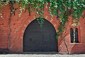 Facade of red brick retro style house with black wooden gate at entrance in Italy.