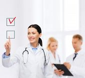healthcare, medicine and technology concept - smiling female doctor pointing to checkbox