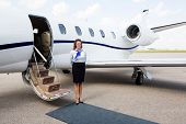 Full length portrait of airhostess standing by private jet at airport terminal