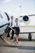 Full length portrait of confident airhostess and pilot standing on private jet's ladder at airport t