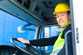 pic of heavy equipment operator  - driver driving with the truck over building or construction site - JPG
