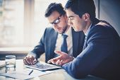 picture of fi  - Image of two young businessmen using touchpad at meeting - JPG