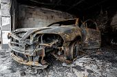 stock photo of scrap-iron  - Close up photo of a burned out cars in garage after fire for grunge use - JPG