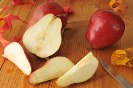 image of anjou  - Sliced red anjou pears on a rustic wooden table with autumn leaves - JPG