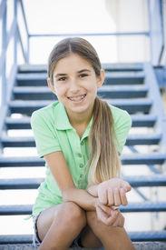 stock photo of tween  - Portrait of Smiling Tween Girl Sitting On Stairway - JPG