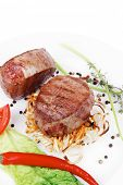 grilled beef fillet medallions with thyme and red hot chili pepper on plate isolated over white back