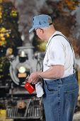 A senior train engineer holding an oil can while waiting for an old steam engine to come to a stop.  Shallow DO.