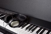 Close-up headphones on piano keyboard on black backround