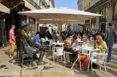 LISBON, PORTUGAL - MARCH 17: The crowded terrace of Cafe A Brasileira with the Statue of Fernando Pe