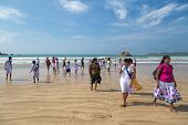 WELIGAMA, SRI LANKA - MARCH 7, 2014: Group of local people walking on sandy beach. Weligama is one o