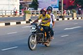 GALLE, SRI LANKA - MARCH 7, 2014: Local men riding motorcycle on street of Galle. Motorcycling is one of main transportation for the local people in the country.