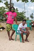 WELIGAMA, SRI LANKA - MARCH 7, 2014: Two young local surfers posing on beach. These young men rent o